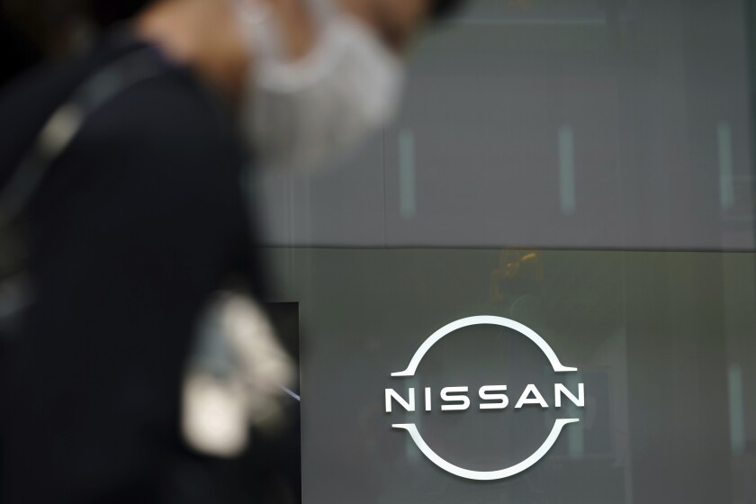 FILE - In this May 11, 2021, file photo, a man wearing a face mask to to help curb the spread of the coronavirus walks by the logo of Nissan Motor Co.'s showroom in Tokyo. Nissan reported Wednesday, July 28, 2021 a 114.5 billion yen ($1 billion) profit for the April-June quarter as its sales and profitability improved, especially in the U.S. market. (AP Photo/Eugene Hoshiko, File)