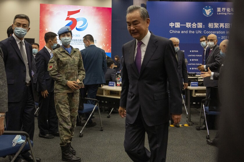 A Chinese United Nations peacekeeper looks on as Chinese Foreign Minister Wang Yi leaves after speaking at a symposium to mark the 50th anniversary of the People's Republic of China's entry into the U.N. at the Foreign Ministry in Beijing on Friday, June 25, 2021. Foreign Minister Wang Yi said China remains deeply committed to United Nations peacekeeping efforts, where more than 2,400 Chinese troops and police are serving, a contribution that underscores China's increasing prominence in the world body. (AP Photo/Ng Han Guan)