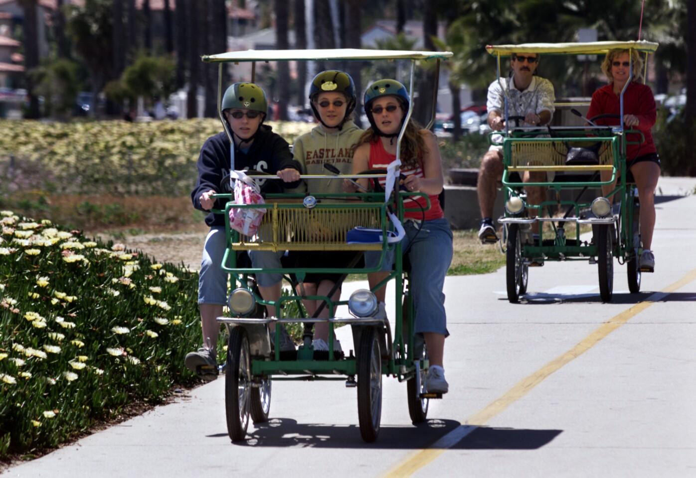 MA group in a surrey pedals along a bike path that runs along the beach.