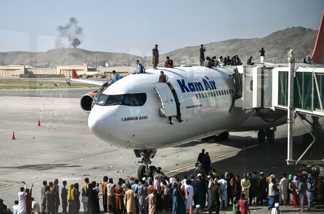 مردم در فرودگاه بین المللی کابل سوار هواپیما می شوند.