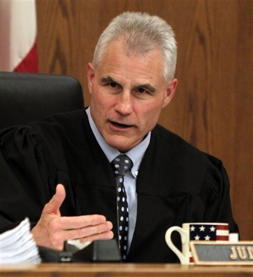 """FILE In this June 6, 2011 file photo, Cuyahoga County Common Pleas Court Judge Dick Ambrose talks in his Cleveland court room as jury selection proceeds in the trial of Anthony Sowell. Ambrose, a former Cleveland Browns linebacker known as """"Bam Bam"""", is presiding over the high-profile trial of Sowell, accused of killing 11 women and hiding their bodies in and around his home. (AP Photo/Marvin Fong, Pool)"""