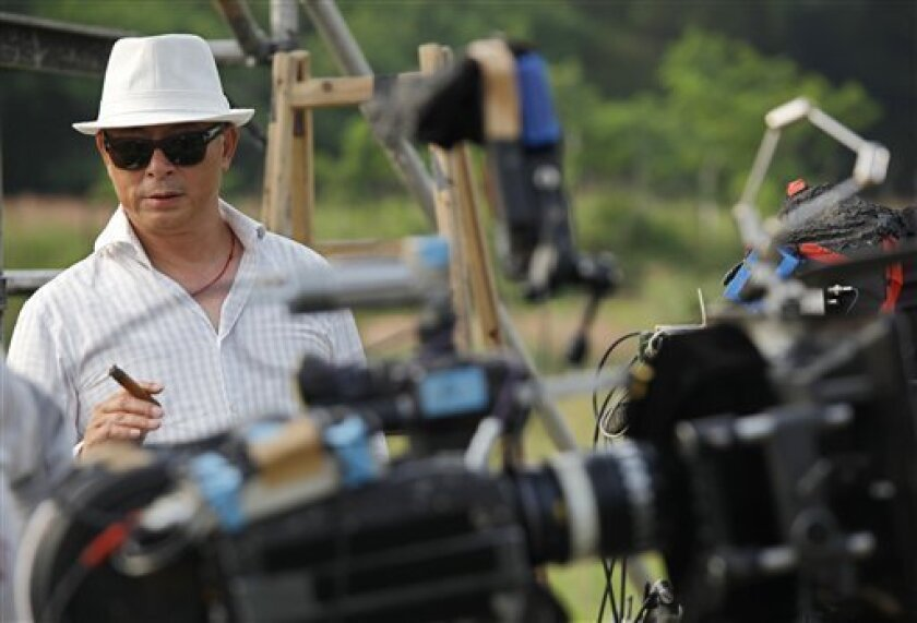 """Hong Kong director Johnnie To stands near a camera during a film shoot of his new movie """"Romancing in Thin Air"""" in Hong Kong, Thursday, June 2,  2011. (AP Photo/Vincent Yu)"""