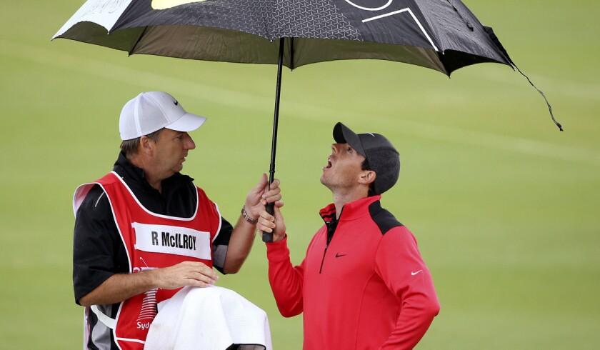 Rory McIlroy and caddie J.P. Fitzgerald seek shelter under an umbrella.