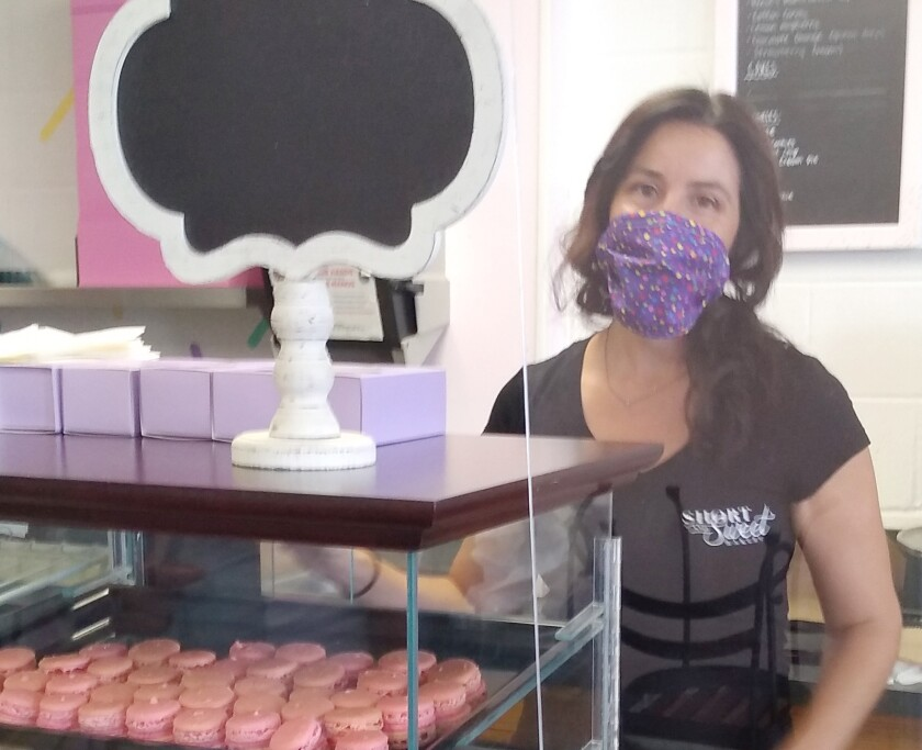 Short and Sweet Bakery co-owner Regina Zetterberg selects treats during the shop's recent grand opening.