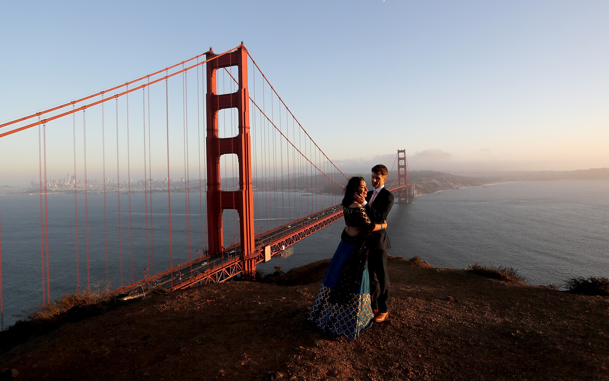 Newlyweds Tulika Jha and Mike Borden take in the sunset at an overlook above the Golden Gate Bridge in San Francisco.