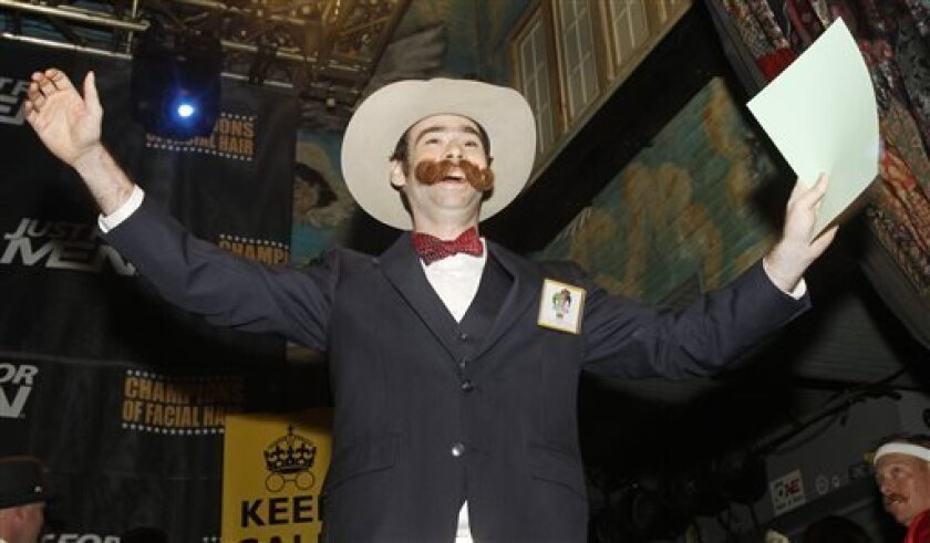 Devon Holcombe of Jacksonville, Fla., greets the crowd before continuing on to win the gold medal in the Natural Moustache division during the fourth annual Just For Men National Beard and Moustache Championships at The House of Blues Saturday, Sept. 7, 2013 in New Orleans. Contestants competed in 18 different categories including Dali, full beard natural and sideburns. (AP Photo/Susan Poag)