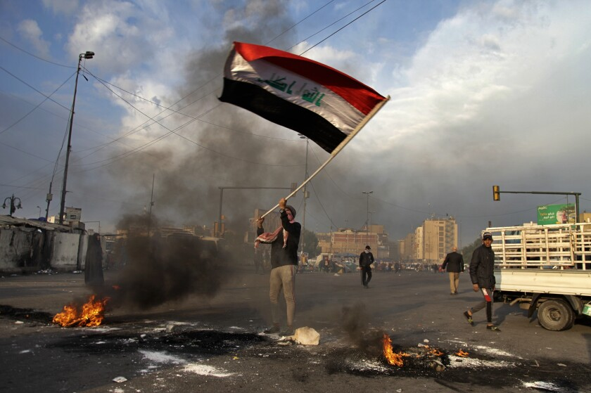 A protester waves the national flag as fires are set to close off streets near Baghdad's Tahrir Square
