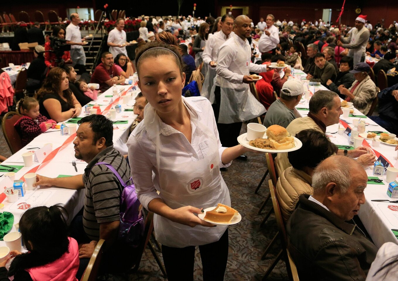 Salvation Army volunteer Janelle Clanton of Santee looks to serve guests at the 32nd annual Christmas Dinner Friday. 1,800 guests and 350 volunteers gathered at Golden Hall in Downtown Friday to enjoy a warm holiday meal.