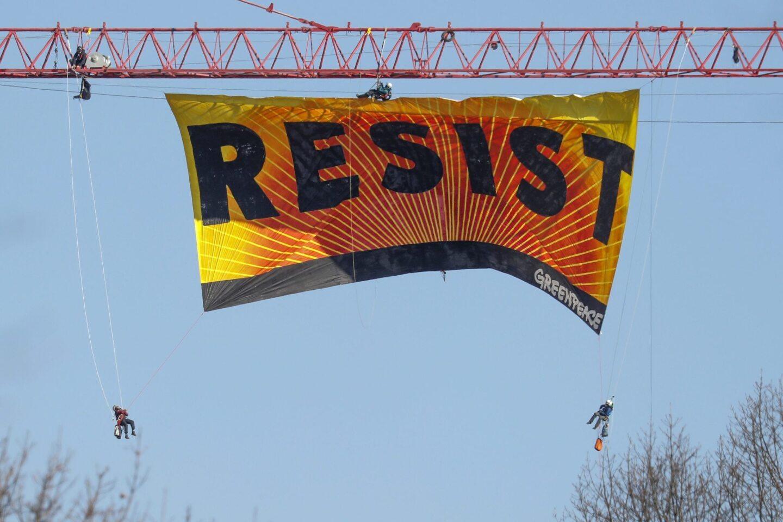 Siete activistas de Greenpeace extienden una enorme manta con la palabra 'RESIST' (Resistir) desde una grúa, cerca de la Casa Blanca en Washington DC.