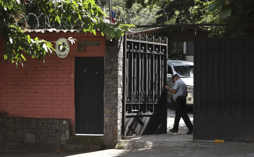A guard opens the gate at Venezuela's embassy in San Salvador, El Salvador, Sunday, Nov. 3, 2019. El Salvador has ordered the expulsion of Venezuelan government diplomats who are loyal to Venezuelan President Nicolás Maduro, joining the U.S. and more than 50 other countries that have said opposition leader Juan Guaidó is Venezuela's rightful president. (AP Photo/Salvador Melendez)