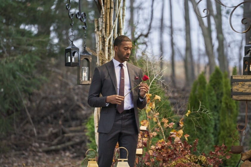 """Matt James, the first Black lead in """"Bachelor"""" history, standing with a rose amid fall foliage."""