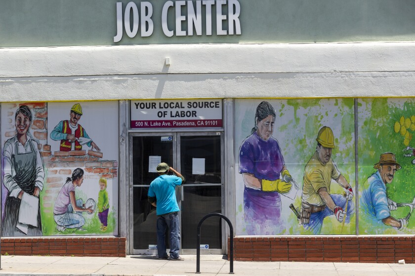 A person looks inside the closed doors of the Pasadena Community Job Center last May.