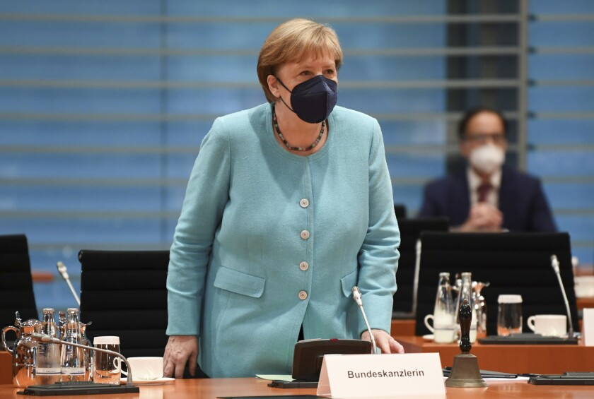 A woman in a pale blue jacket and dark mask stand before a microphone and sign that reads Bundeskanzlerin