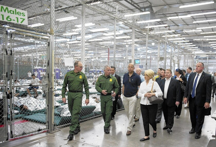 Homeland Security Secretary Jeh Johnson, in short-sleeve shirt, and Arizona Gov. Jan Brewer on June 25 visit a facility in Nogales, Ariz., holding about 900 migrant children. Last month, Johnson sent 60 additional human smuggling investigators to field offices in Houston and San Antonio.