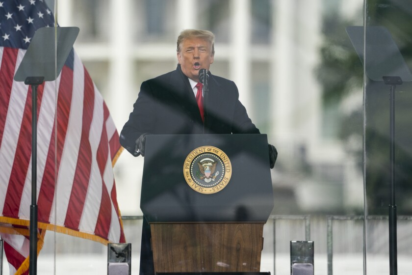 Trump speaks at a podium next to an American flag
