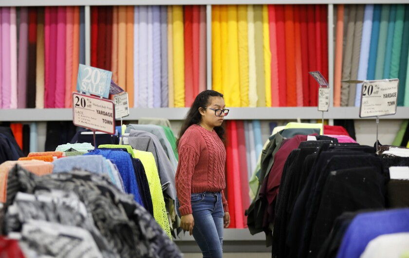 Customer Cindy Roldan walks through Yardage Town in National City, a longtime family fabric business on Dec. 17, 2019. Several of the stores have closed and owner Michael Recht plans to close the rest of them next year.
