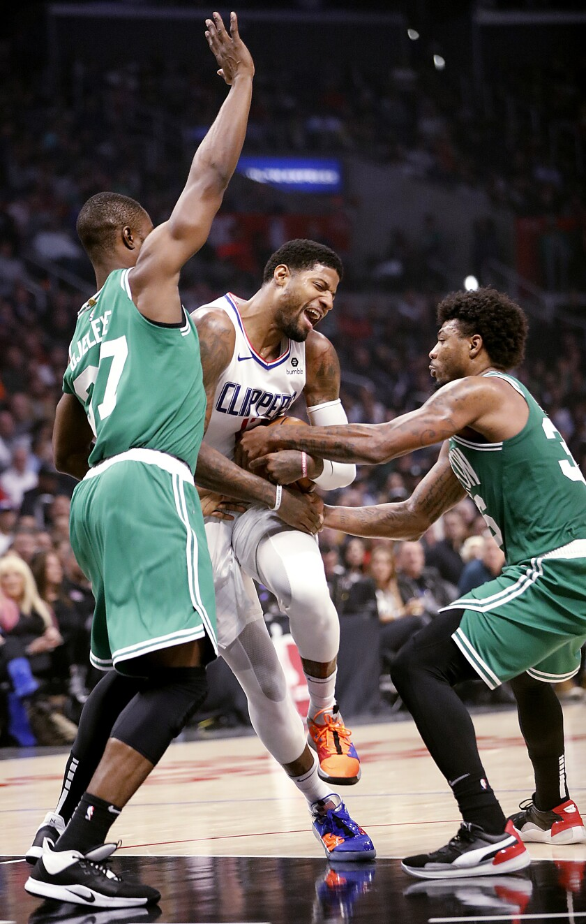 Clippers forward Paul George, center, gets fouled on a drive between Boston defenders Semi Ojeleye and Marcus Smart during the second quarter of their game Nov. 20, 2019, at Staples Center.