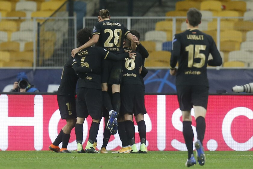 Barcelona's Sergino Dest celebrates with his teammates after scoring his side's opening goal during the Champions League group G soccer match between Dynamo Kyiv and FC Barcelona at the Olimpiyskiy Stadium in Kyiv, Ukraine, Tuesday, Nov. 24, 2020. (AP Photo/Efrem Lukatsky)