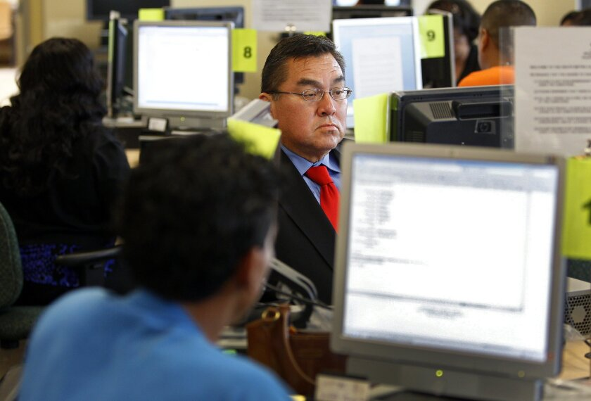 Willie Martinez, who has been out of work for three years, fills out a job application at the Employment Development Department.