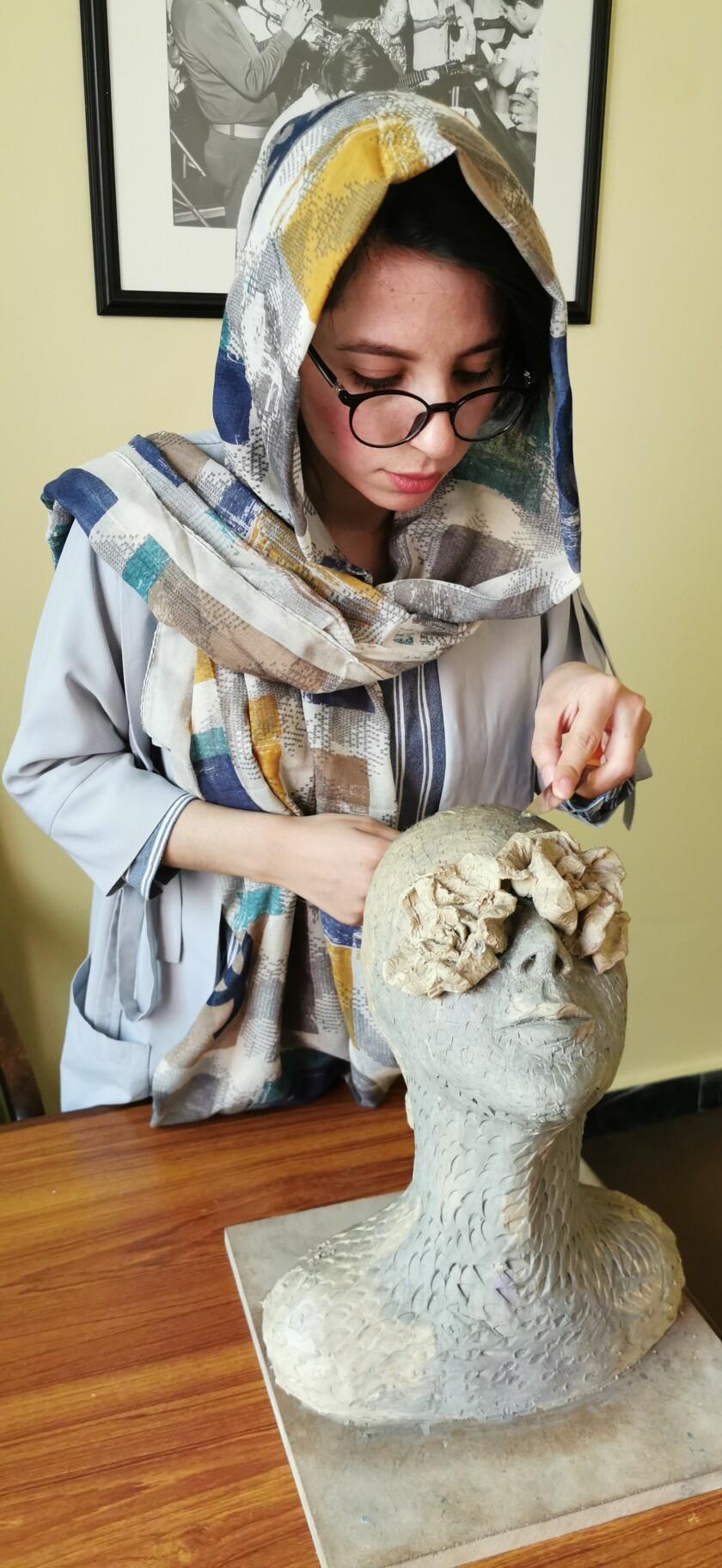 زنی با عینک و روسری با نیم نگاهی به نیم تنه مرد با چشمان بسته است