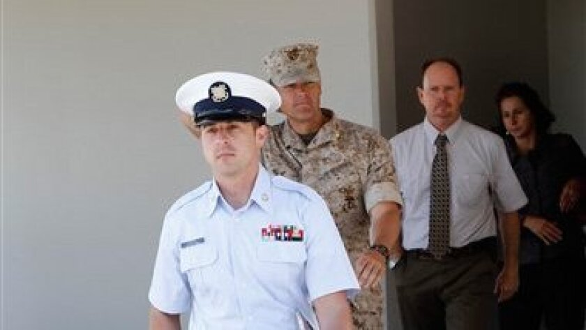 Coast Guard Petty Officer Ian Howell, front, leaves a military court building at Camp Pendleton, Calif., where he was sentenced after pleading guilty to charges of dereliction of duty in the 2009 collision of a Coast Guard vessel and a civilian boat that resulted in the death of an 8-year-old boy, Tuesday, March 29, 2011. Howell will request immediate discharge from the Coast Guard as part of an agreement ahead of his court-martial. (AP Photo/Lenny Ignelzi)