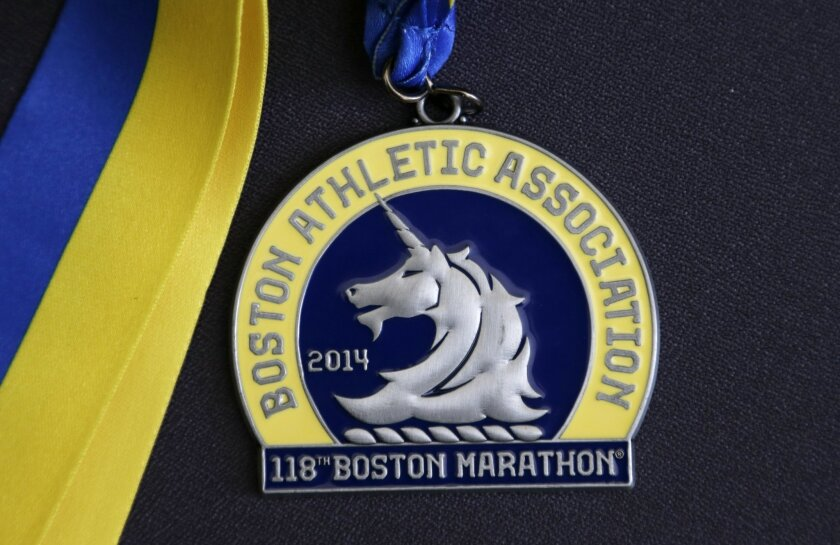 In this Thursday, April 10, 2014 photo, a medal for the 118th Boston Marathon is displayed in Boston. The medal is an example of those to be awarded to each finisher of the 2014 race. More than 5,000 runners were still on the Boston Marathon course when the bombs went off near the finish line in 2013. So the field was expanded for the 2014 marathon to accommodate them. A total field of 36,000 will be the second-largest in the race's history. (AP Photo/Steven Senne)
