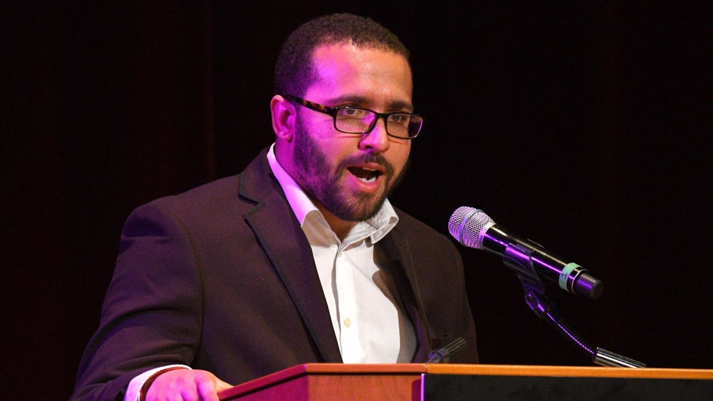 """Wesley Lowery accepts the Christopher Isherwood prize for autobiographical prose for his book """"They Can't Kill Us All"""" at the Los Angeles Times Book Prizes at USC's Bovard Auditorium."""