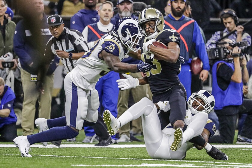 Rams linebacker Corey Littleton, left, and cornerback Aquib Talib tackle New Orleans Saints receiver Michael Thomas during first half in the 2018 NFC championship game in January.