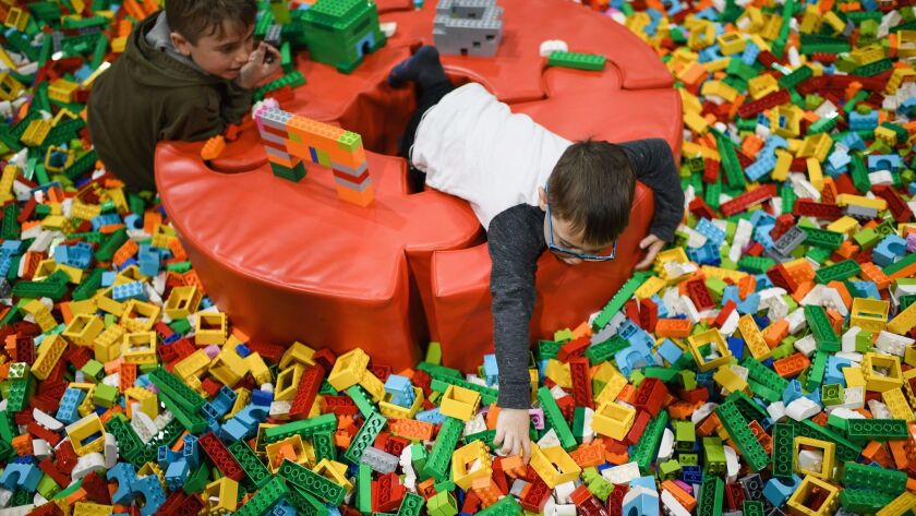 Lego will cut jobs and simplify the company in response to a sales decline. Above, children play at a recent event in Scotland.