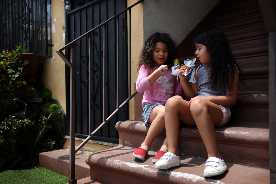 Elizabeth Sanchez, left, 5, and Mia Estrada, 6, eat ice cream at their apartment complex.