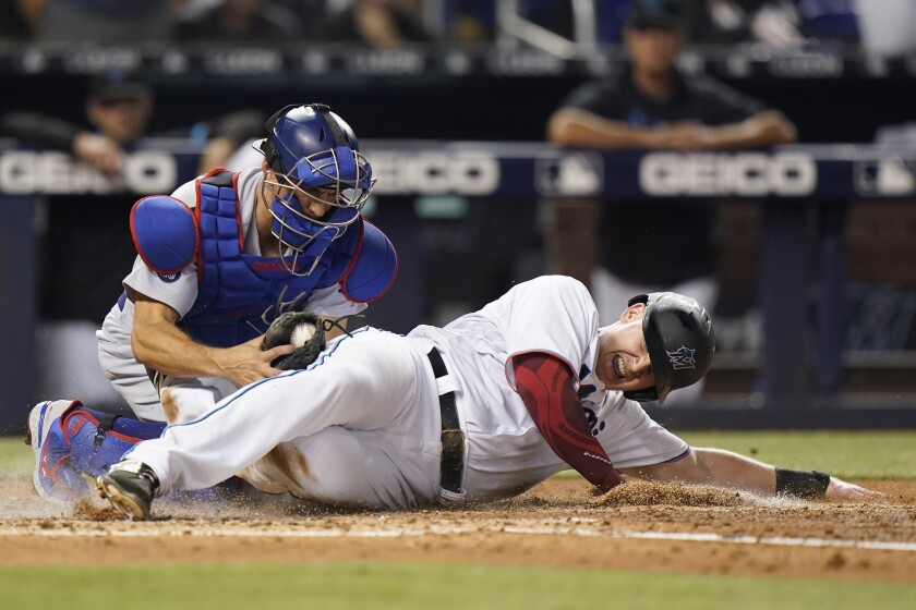 Miami Marlins' Garrett Cooper is tagged out at home by Los Angeles Dodgers catcher Austin Barnes during the third inning of a baseball game, Wednesday, July 7, 2021, in Miami. (AP Photo/Wilfredo Lee)