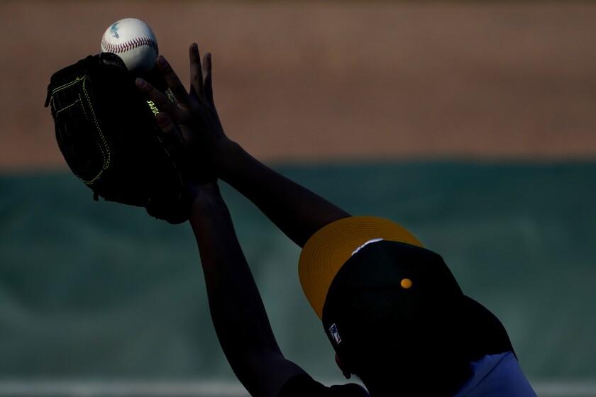 Un fanático atrapa una pelota durante el juego de exhibición entre los Rojos de Cincinnati.
