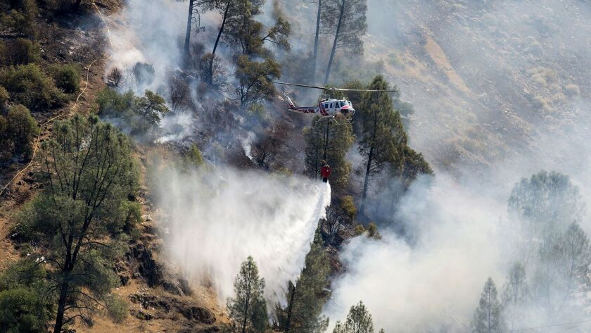 Crews battle the Ferguson fire along steep terrain behind the Redbud Lodge along Highway 140 near El Portal in Mariposa County on Saturday.