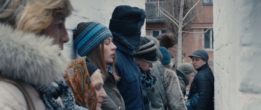 """People wearing cold-weather clothes line up in war-ravaged eastern Ukraine in the movie """"Donbass."""""""