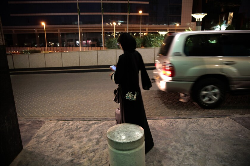 A woman waits for an Uber car at a shopping mall in Riyadh, Saudi Arabia. Since women are not allowed to drive in the conservative kingdom, they must hire cars or rely on a male relative to ferry them around.
