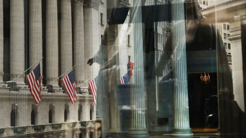 Flags along the New York Stock Exchange are reflected in the window of Federal Hall.