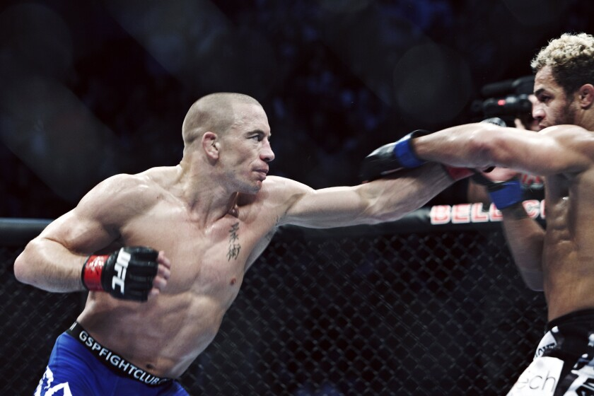 Georges St-Pierre, left, throws a punch in a fight against Josh Koscheck on Dec. 11, 2010.