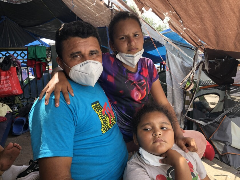 Abel Garcia, an asylum seeker from Honduras, with daughters Andrea, 11, and Ashley, 7, at the Reynosa camp