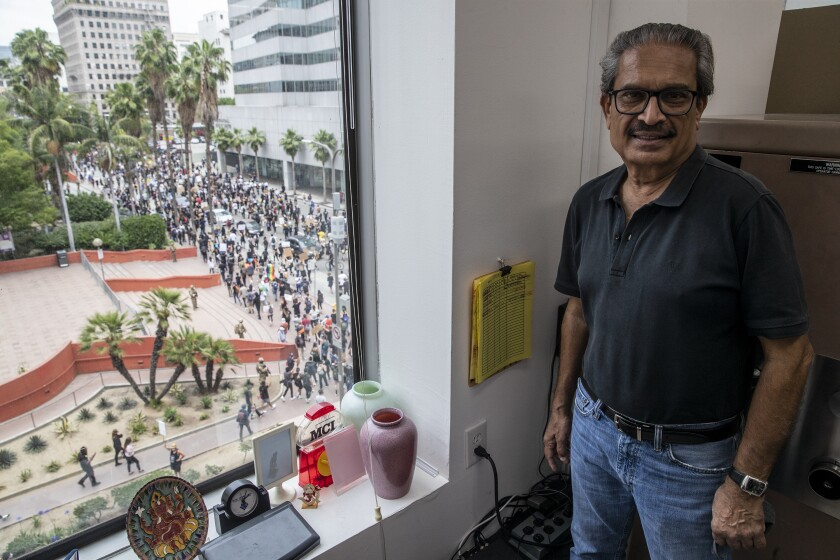 Sanat Shah, owner of Shah Jewel Inc., looks out over Pershing Square where hundreds of protesters march.