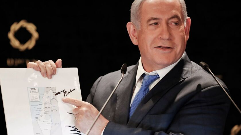 Israeli Prime Minister Benjamin Netanyahu, speaking May 30 to the media, points to the Golan Heights on a map of Israel featuring a note and signature from President Trump.