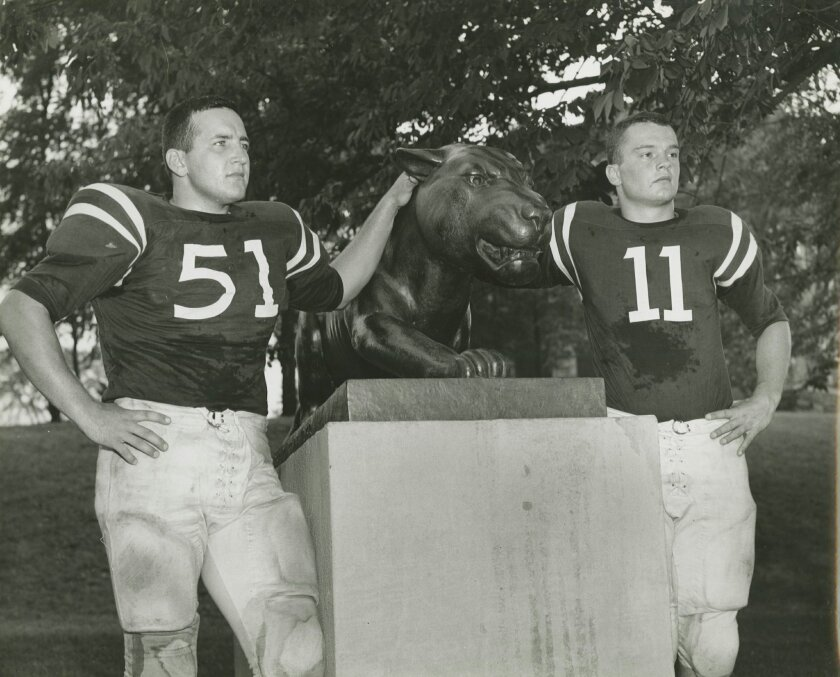 In a 1964 photo provided by Lafayette College, Lafayette College football players Douglas Gifford, left, and George Hossenlopp pose next to a statue in Easton, Pa. On Saturday, Nov. 22, 2014, Lehigh University will play Lafayette College for the 150th time, at Yankee Stadium in New York. (AP Photo/Lafayette College Archives)