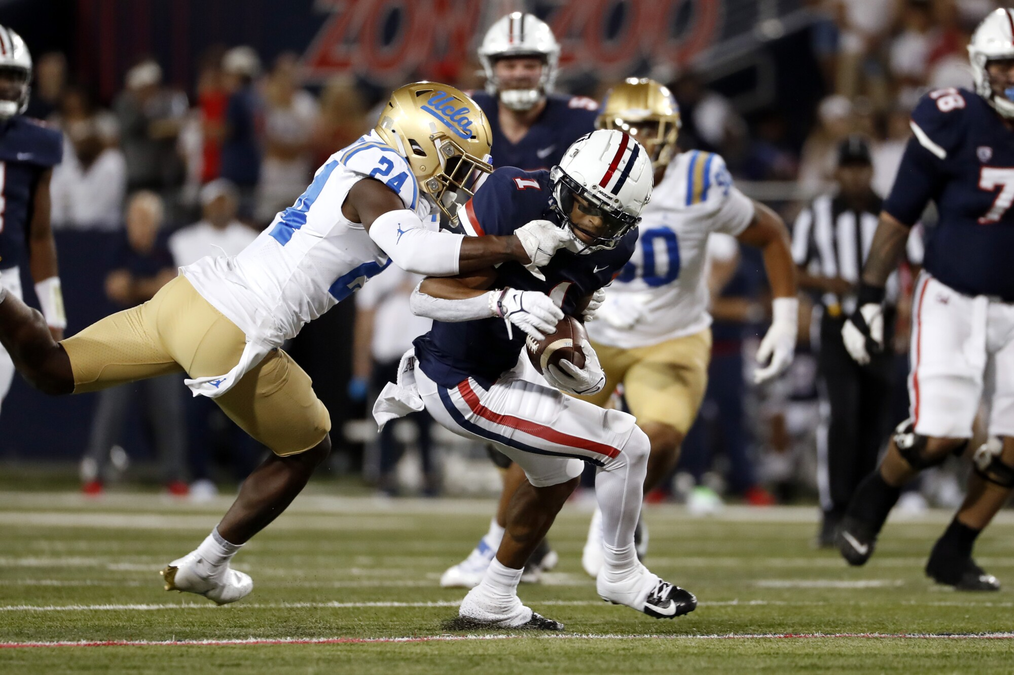 Arizona wide receiver Stanley Berryhill III is tackled by UCLA defensive back Qwuantrezz Knight