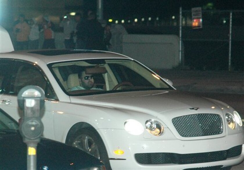 An assault suspect sits in a Bentley with police officers behind him in the North Hollywood section of Los Angeles Monday Feb. 9, 2009. The man led police through the Los Angeles area in a slow-speed pursuit that ended in a stand-off. (AP Photo/Mike Meadows)