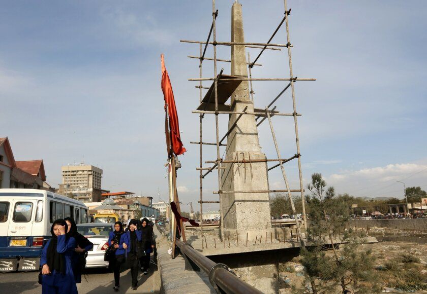 Afghan young ladies walk past, an unfinished monument dedicated to Farkhunda who was beaten to death by a mob in March 2015 after being falsely accused of burning a Quran, in Kabul, Afghanistan, Wednesday, Nov. 4, 2015. A 22-year-old Afghan woman was thrown in a hole in the ground and stoned to dea