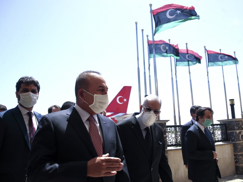 FILE - In this June 17, 2020, file photo, Turkey's Foreign Minister Mevlut Cavusoglu, left, and Muhammed Tahir Siyala, Foreign Minister of Libya's internationally-recognized government, speak at the airport, in Tripoli, Libya. Libya's eastern-based forces have lost the chance to engage in a political solution to the North African country's conflict, Turkey's foreign minister said Saturday, June 20, 2020. (Fatih Aktas/Turkish Foreign Ministry via AP, Pool, File)