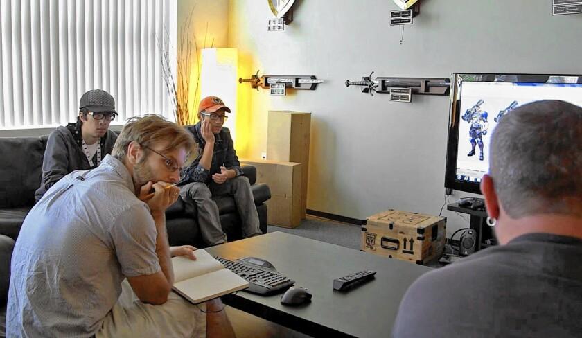 "Blizzard Entertainment's senior game producer Lee Sparks, left, assistant art director Arnold Tsang and senior concept artist Ben Zhang listen as senior Vice President Chris Metzen discusses early designs for ""Overwatch."""