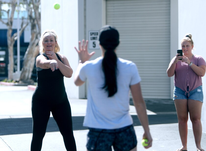 The Packaged Deal softball school co-founder Jen Schroeder, left, plays catch with co-founder Morgan Stuart, center, as Kayleen Shafer captures the action for hundreds of Facebook Live viewers outside her business in Anaheim on Tuesday. The class was for drills and skills softball students can do alone at home.