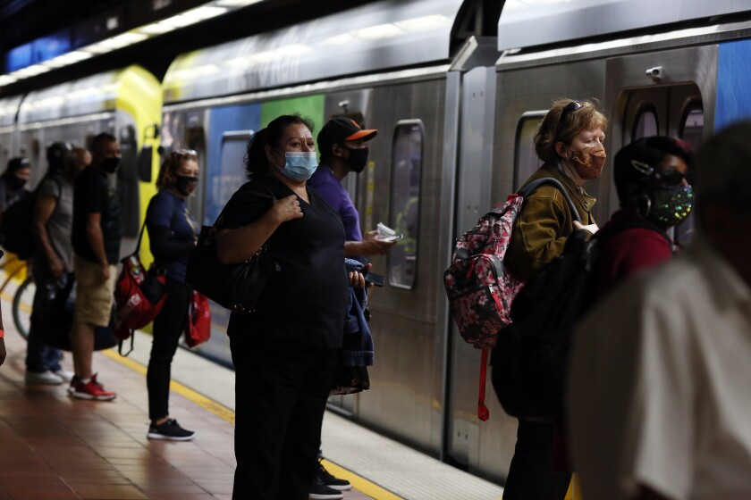 Transit riders wearing face masks and carrying backpacks stand on a train platform