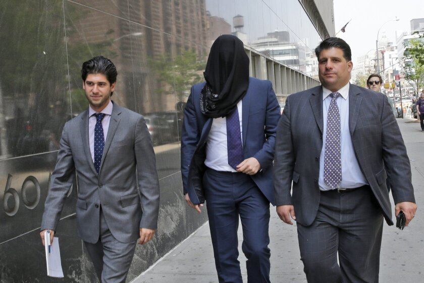 Wojciech Braszczok is led into the court with his face covered Tuesday in New York.
