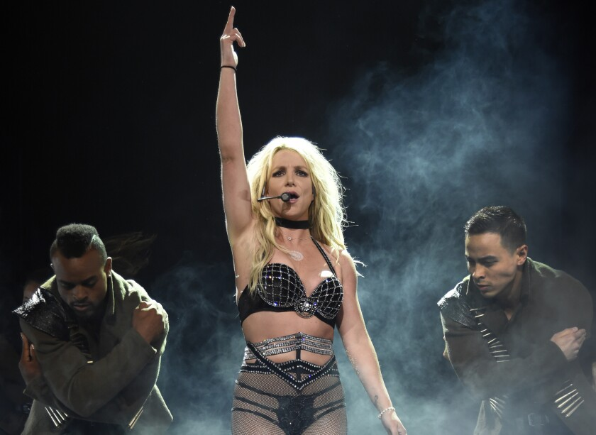 Britney Spears, in a sparkly bikini outfit, sings into a headset onstage.